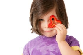 Young girl holding up a pepper